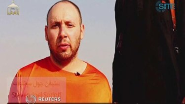 This image from video posted on the internet by Islamic State militants purports to show journalist Steven Sotloff before he was beheaded.