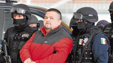 Drug lord Eduardo Teodoro Garcia Simental is escorted by police in Mexico City.