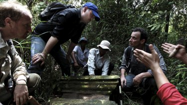 Rock gods: Australian archaeologist Damian Evans (blue cap) inspects a find with Jean-Baptiste Chevance (kneeling on the right) in Cambodia.