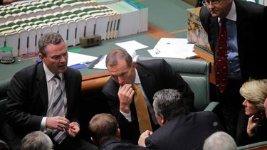 Tony Abbott in deep discussion with frontbenchers.
