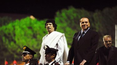 Side by side ... Muammar Gadaffi, left, and Silvio Berlusconi arrive at an Italy-Libya friendship celebration during Mr Gadaffi's two-day visit.