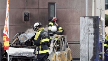 Firefighters investigate the scene of one of the explosions in Utsunomiya, north of Tokyo.