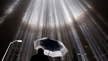 A worker holds an umbrella while adjusting beams of the Tribute in Lights ahead of the 10th anniversary of the September 11 terrorist attacks in New York City.