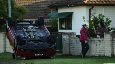 Rachna Aggarwal (right) talks to a neighbour near an overturned car on the corner of Clarence Street and Fulton Avenue, Constitution Hill, Sydney.