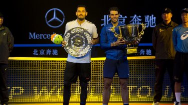 Rafael Nadal and Nick Krygios pose with their trophies after the men's singles final match in the China Open.