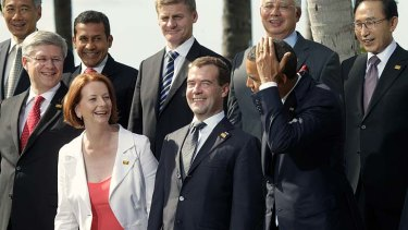 Plenty of smiles but no silly shirts ...  President Barack Obama jokes about grooming his hair with  Julia Gillard during the group photo call at the APEC leaders' meeting in Hawaii yesterday as Russian President Dmitry Medvedev chuckles.
