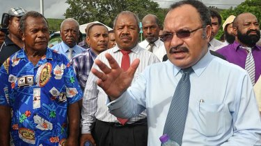 Papua New Guinean Prime Minister Peter O'Neill (right) addresses the crowd outside Government House in Port Moresby.