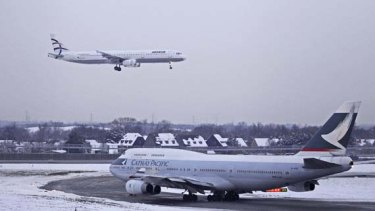 A passenger jet comes in to land as a Cathay Pacific Boeing 747 taxis at Heathrow Airport. Snow and freezing temperatures further delayed flights across northern Europe.
