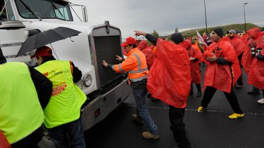 Spiros Cechris jumps in front of a truck as workers block the entrance to Coles' national distribution centre.