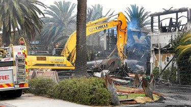 A crane removes the roof of the still-smouldering Stokehouse.