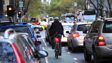 A cyclist navigates his way through the traffic on Collins st.