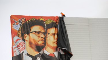 Workers remove a poster for The Interview from a billboard in Hollywood, California, a day after Sony announced was cancelling the movie's Christmas release.