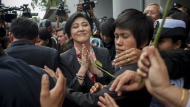 Thai Prime Minister Yingluck Shinawatra receives roses from her supporters.