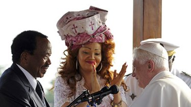 Cameroon President Paul Biya and his wife Chantal, wearing a festive bonnet, welcome Pope Benedict.