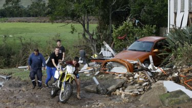 A motorbike is retrieved from the flood detritus.