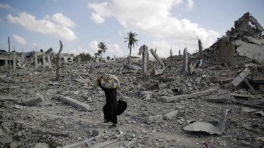 A Palestinian woman carries belongings from the remains of Khuza'a.