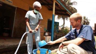 Dr. Kent Brantly, one of the two Americans who contracted Ebola, works at an Ebola isolation ward at a mission hospital outside of Monrovia, Liberia before contracting the virus.