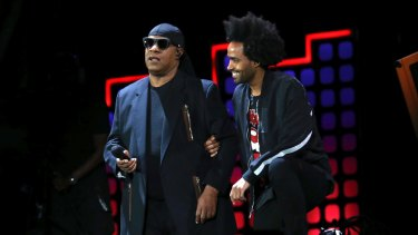 Stevie Wonder, left, kneels on stage next to his son Kwame Morris before performing at the Global Citizen Festival in Central Park on Saturday.