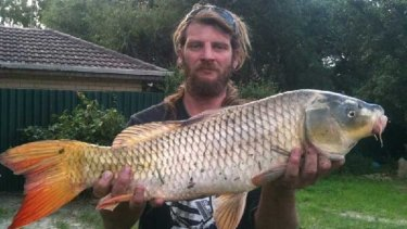 Clay Anderson with the giant carp caught in a man-made lake in Thornlie.