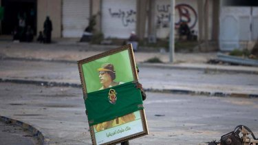 A soldier carries a portrait of Colonel Gaddafi in Misrata during a trip organised by Libyan authorities.