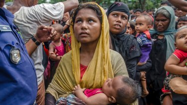 Rohingya Muslim women, who crossed over from Myanmar into Bangladesh, hold their children as they wait to receive aid near Balukhali refugee camp,.