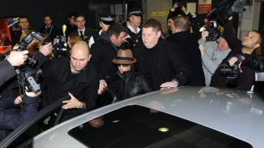 Split ... British singer Cheryl Cole is surrounded by photographers as she leaves London's Heathrow Airport.