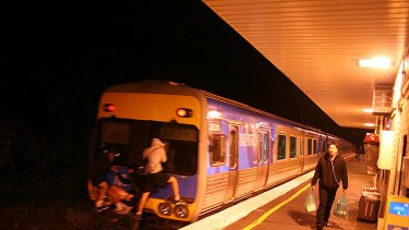 Three people cling to the back of a moving train at Hughesdale station overnight.