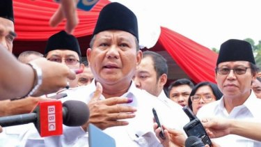 Indonesian presidential candidate Prabowo Subianto speaks to the media after voting on Wednesday. He and his rival Joko Widodo have claimed victory.