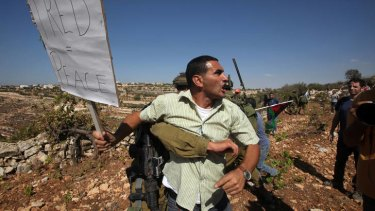 A Palestinians demonstrator is restrained by an Israeli soldier as he tries to reach Palestinian lands to pick grape and olive trees, near the fence of the Israeli settlement of Karmi Tsour, north of the West Bank town of Hebron.