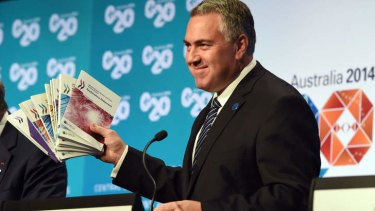 Optimistic: Treasurer Joe Hockey  holds up a report during a press conference at the G20 Finance Ministers and Central Bank Governors Meeting in Cairns on Saturday.