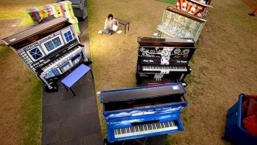 Nellie Bell amongst the pianos.