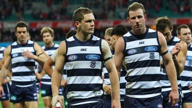 Glum Geelong players return to the dressing room after being beaten by the Swans.