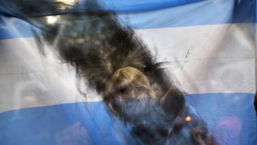 A woman holds up an Argentine flag smeared with black paint as people gather near the funeral home where a private wake was held for Alberto Nisman.