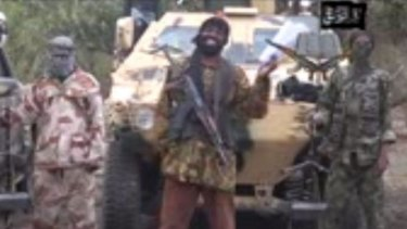 A still from a video that shows the leader of the Islamist extremist group Boko Haram Abubakar Shekau (centre) threatening to sell hundreds of girls his group abducted from a Chibok school in the northern state of Borno.