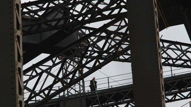 The protester speaks on his mobile phone after unfurling banners on the Sydney Harbour Bridge.