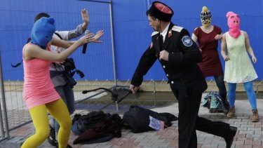 A Cossack militiaman attacks Tolokonnikova and a photographer.