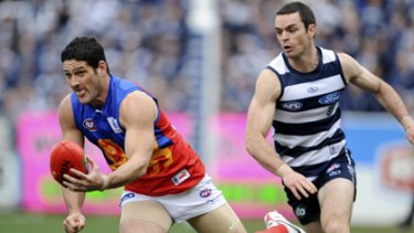 Matthew Scarlett chases after Brendan Fevola, who kicked only one goal against the Cats.