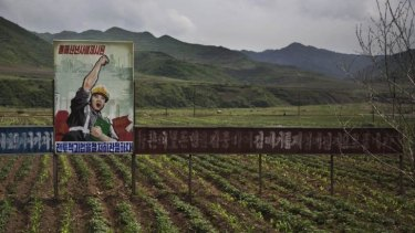 A propaganda billboard stands in a field south of Samsu, in North Korea's Ryanggang province.