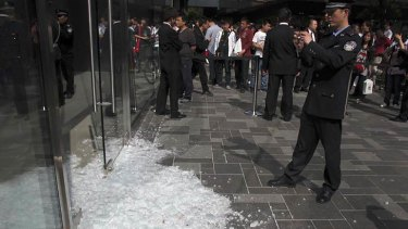 In this photo taken Saturday 7 May, 2011, a Chinese policeman takes photos of the broken glass door in the aftermath of a scuffle at Apple's Sanlitun retail store in Beijing, China.