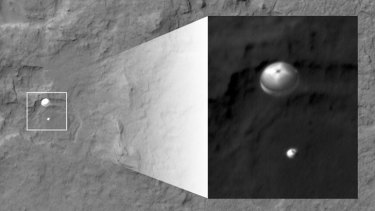 Touchdown ... In this image, NASA's Curiosity rover and its parachute, left, descend to the Martian surface.
