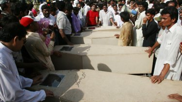 Relatives lay out the caskets of the victims in Gojra.