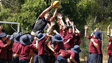 Justin Koschitzke flies for a mark over students from Tyabb Primary School.