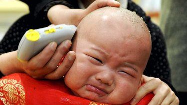 Stressed out ... a child gets a haircut in Hefei, Anhui province.