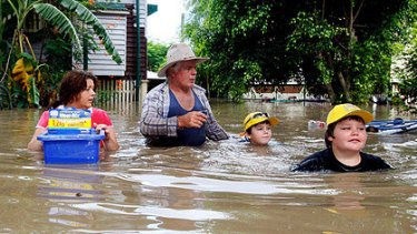 Paul Barnes and Mandy Greene with their sons, Patrick, right, and Bradley, wade through chest-high water to return to their house to find their insurance documents in Rockhampton yesterday.