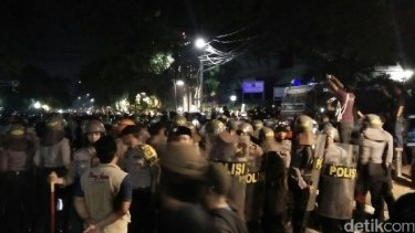 Indonesian police attempt to control a crowd protesting against a meeting of 'communists' in Jakarta.