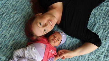 Melissa Murray with her seven-week-old daughter, Leilani, on her lounge room floor where she gave birth.