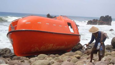 A man walks near a lifeboat in Central Java which used by Australia to send asylum seekers back to Indonesia.