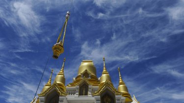 Hundreds of people attended a  ceremony at the Wat Dhammadharo Buddhist temple in Lyneham, where a crane lifted a golden tiered umbrella on to the main dome of the partly constructed pagoda.