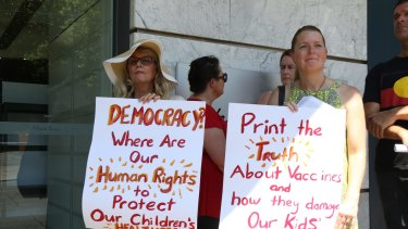 Women hold up signs criticising vaccination in Australia.
