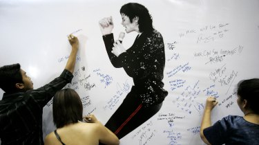 Fans write condolence notes beside Michael Jackson portrait during a rally in memory of him in Kuala Lumpur, Malaysia.